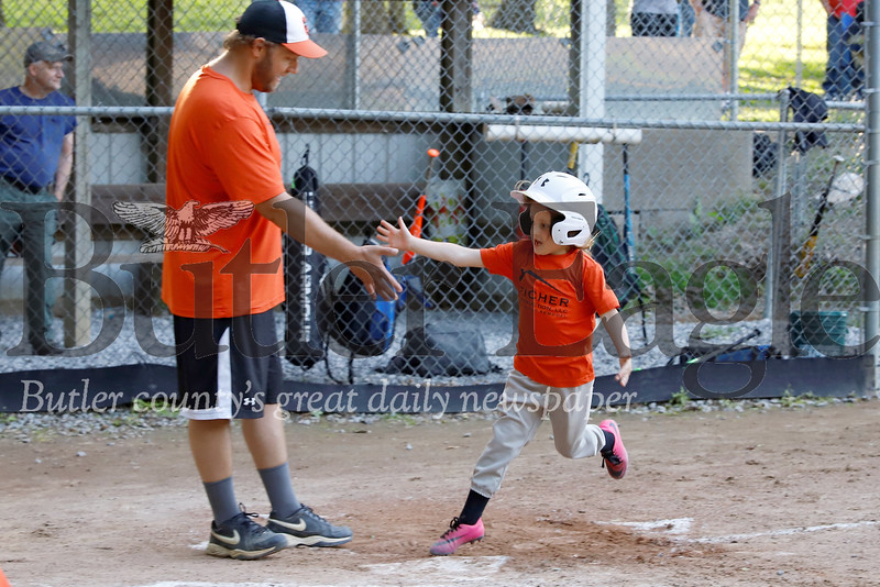 Maddi Giles high fives assistant coach Jeremy Miller on her way to scoring in the 4-6 year-old little league game between the Pirates and Orioles Friday at Laura Doerr Park Friday, June 14. Seb Foltz/Butler Eagle
