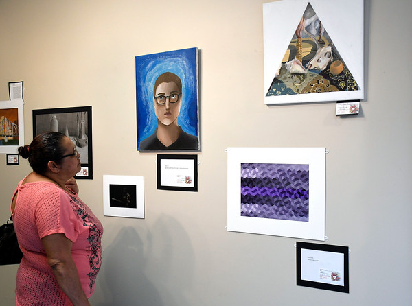 5/1/2018 Mike Orazzi | Staff Porfirio Rivera admires some of the artwork on display during the Community Art Show held at the Bristol Board of Education Tuesday evening.