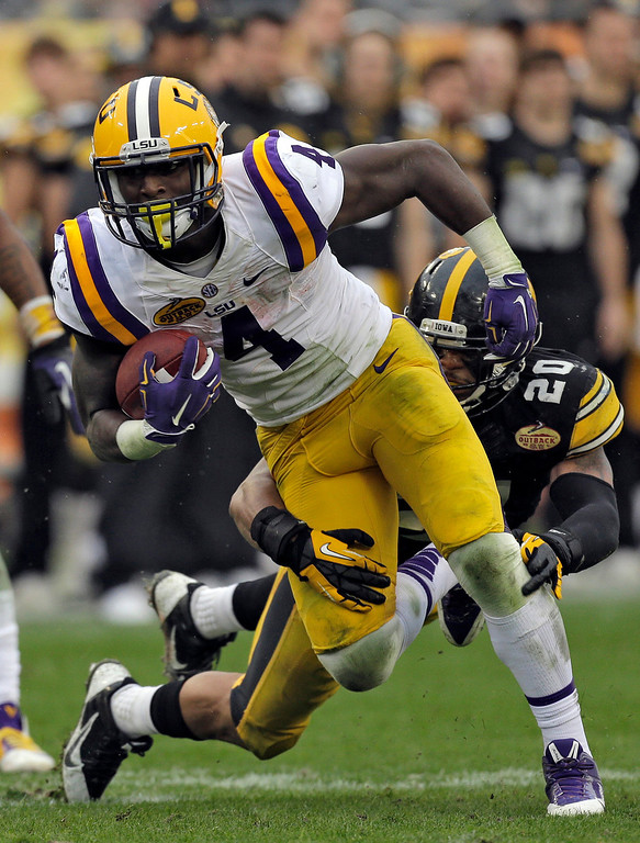 . LSU running back Alfred Blue (4) is wrapped up by Iowa linebacker Christian Kirksey (20) during the second quarter of the Outback Bowl NCAA college football game Wednesday, Jan. 1, 2014, in Tampa, Fla. (AP Photo/Chris O\'Meara)
