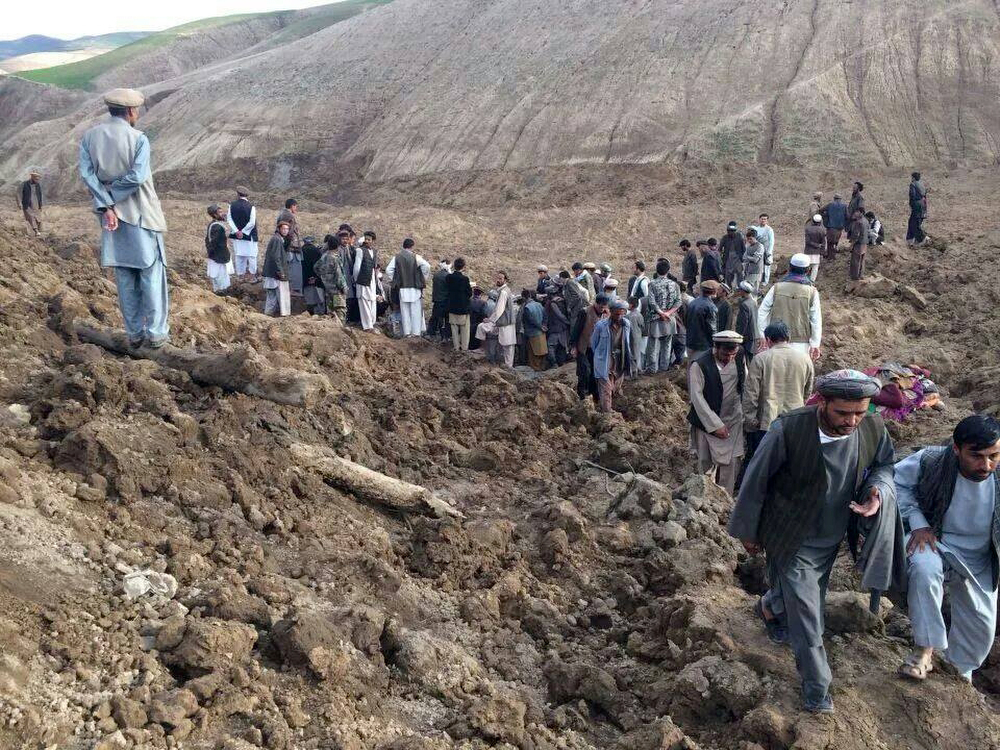 . In this photo provided by Homayoon Rahmani, the chief of road reconstruction program in the Afghan Rural and Rehabilitation Development Ministry, Afghans search for survivors after a massive landslide landslide buried a village Friday, May 2, 2014 in Badakhshan province, northeastern Afghanistan, which Afghan and U.N. officials say left hundreds of dead and missing missing.(AP Photo/Homayoon Rahmani)