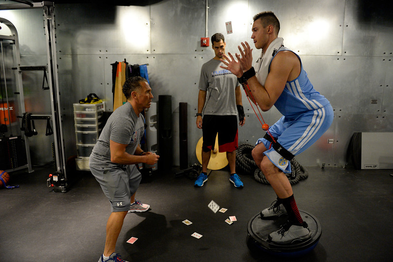 . Denver Nuggets Danilo Gallinari balances on a balancing ball catching playing cards that are tossed by assistant coach/strength and conditioning coach Steve Hess May 27, 2014 at Pepsi Center. (Photo by John Leyba/The Denver Post)