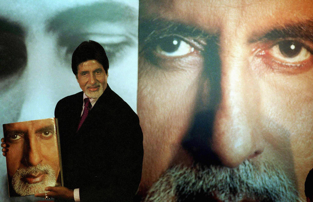 . (FILES) In this picture taken 11 October 2002, Indian film actor Amitabh Bachchan poses in front of portaits of himself as he displays a book by his wife Jaya Bachchan, during his 60th birthday celebration in Bombay.  An Indian newspaper reporter, Hussain Zaidi of Bombay\'s tabloid Mid-Day wrote 12 September, that whilst on a recent visit to Iraq, he was abducted by gangsters but was freed after he promised to arrange a meeting between his gun-wielding captors and Bollywood icon Bachchan.  STR/AFP/Getty Images