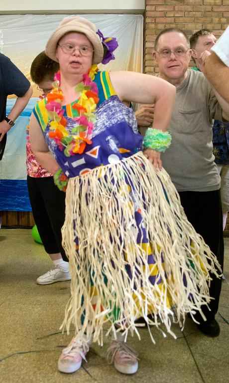 . Duncan Scott/DScott@News-Herald.com Claudia Beifus learns a hula dance during a luau on June 18 at the Lake County Board of Developmental Disabilities/Deepwood Vocational Guidance Center.
