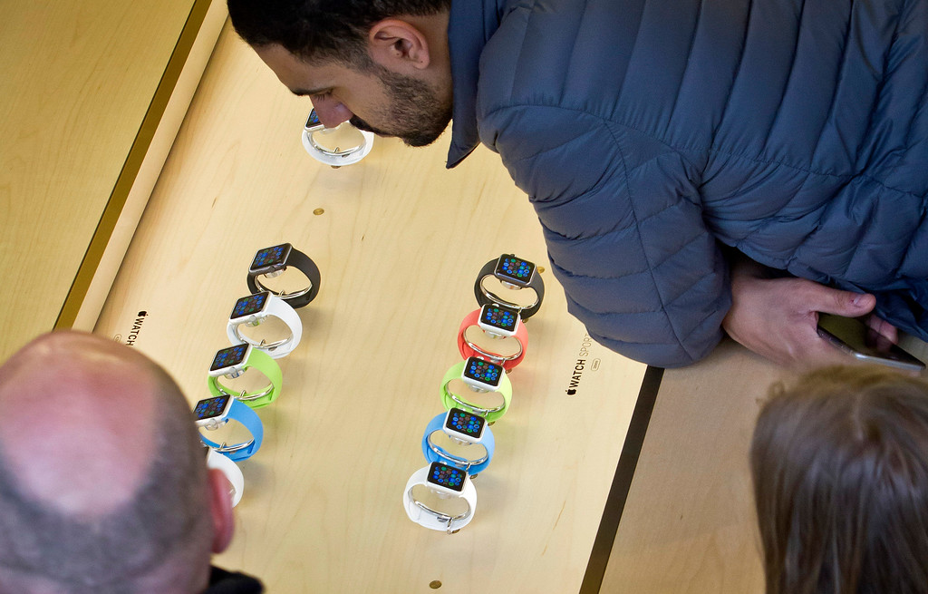 . Customers look at Apple\'s new watch, displayed inside a glass case, Friday, April 10, 2015, in New York. The watch is selling in eight countries and Hong Kong, with shipments scheduled to start April 24. (AP Photo/Bebeto Matthews)