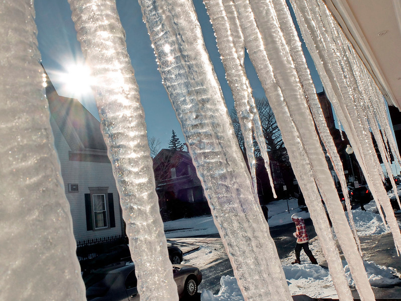 . A man crosses Elm Street beyond icicles hanging from the gutter of a building Wednesday, Jan. 23, 2014, in New Bedford, Mass.  (AP Photo/The Standard-Times, Peter Pereira)