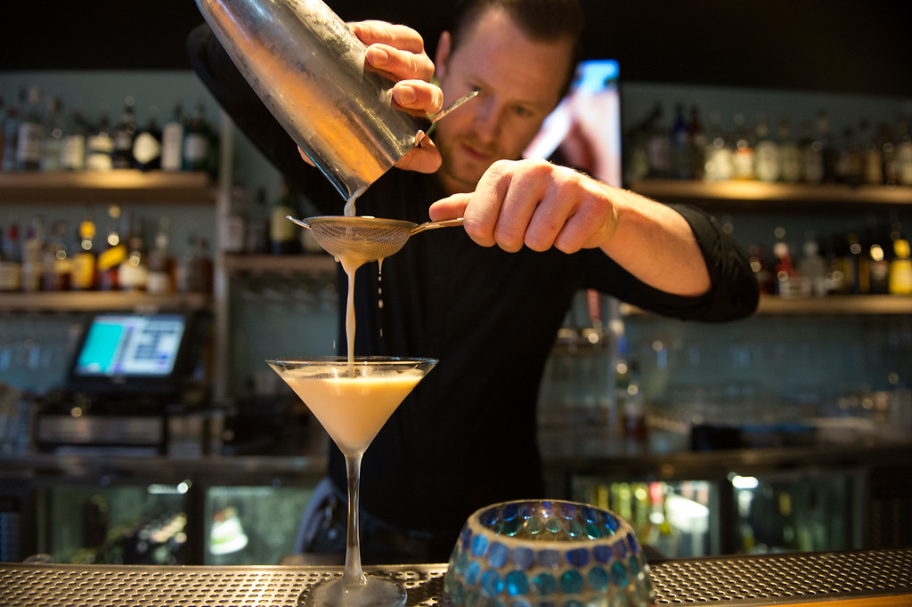 """. Bar manager Charles Kollmann strains the \""""Hey Hey Brûlée\""""  cocktail at the happy hour at  the D Bar Denver on Friday, February 26, 2016.  (Photo by Cyrus McCrimmon/ The Denver Post)"""