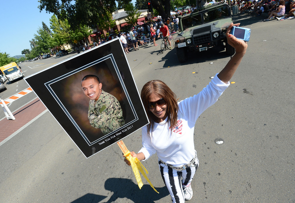 . Shirley Kocourek, of Danville, a member of the Blue Star Moms, holds a photo of her son Brendon Antrea, who is serving in the Navy, as she and other Blue Star Moms walk down San Ramon Valley Boulevard during the 4th of July Parade in Danville, Calif., on Thursday, July 4, 2013. The parade, sponsored by the Kiwanis Club of San Ramon Valley, features about 120 entries with an estimated 40,000 spectators attending. (Doug Duran/Bay Area News Group)