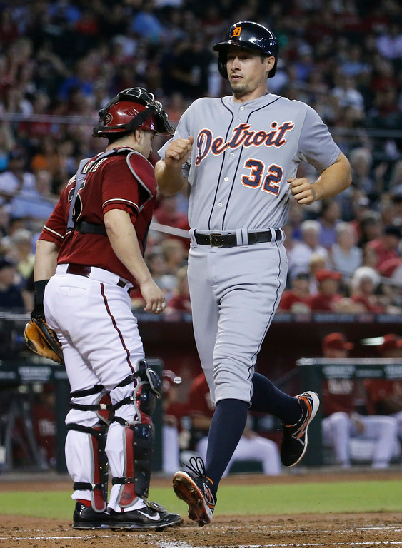 . Detroit Tigers\' Don Kelly (32) scores on a two-RBI double by teammate Alex Avila as Arizona Diamondbacks catcher Miguel Montero waits for the throw during the second inning of a baseball game, Wednesday, July 23, 2014, in Phoenix. (AP Photo/Matt York)