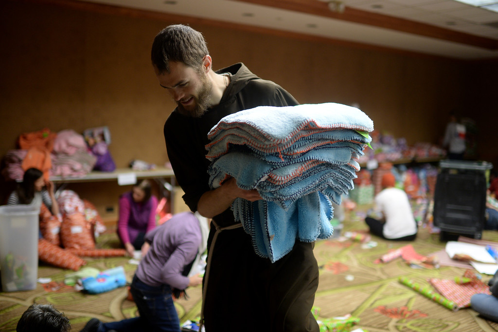 ". DENVER, CO. DECEMBER 21: Brother Donald is gathering the blankets during the annual Father Woody Christmas Party in Denver, Colorado December 21, 2013. In advance of handing out 5,000 gifts, volunteers are doing a ""wrapping party\"" at the Sheraton Denver Downtown Hotel. (Photo by Hyoung Chang/The Denver Post)"