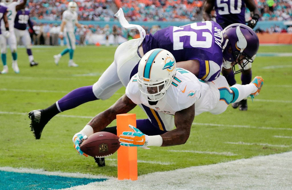 . Miami Dolphins wide receiver Mike Wallace (11) scores a touchdown as Minnesota Vikings free safety Harrison Smith (22) is late with the tackle during the second half of an NFL football game, Sunday, Dec. 21, 2014, in Miami Gardens, Fla. (AP Photo/Lynne Sladky)