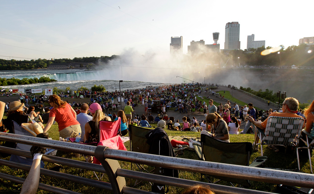 . A crowd gathers to watch Nik Wallenda walk across Niagara Falls on a wire in Niagara Falls, N.Y., Friday, June 15, 2012. (AP Photo/David Duprey)