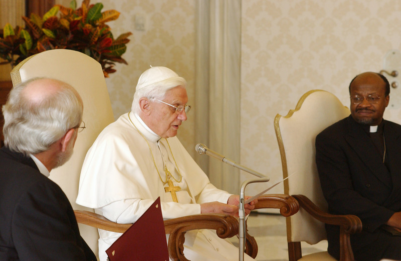 Pope Benedict XVI delivered a prepared statement Nov. 7, 2005, to a delegation from the Lutheran World Federation (LWF) in the library of his Vatican residence as the Rev. Mark S. Hanson (left), LWF president, Chicago, and the Rev. Ishmael Noko (right), LWF general secretary, Geneva, listened.