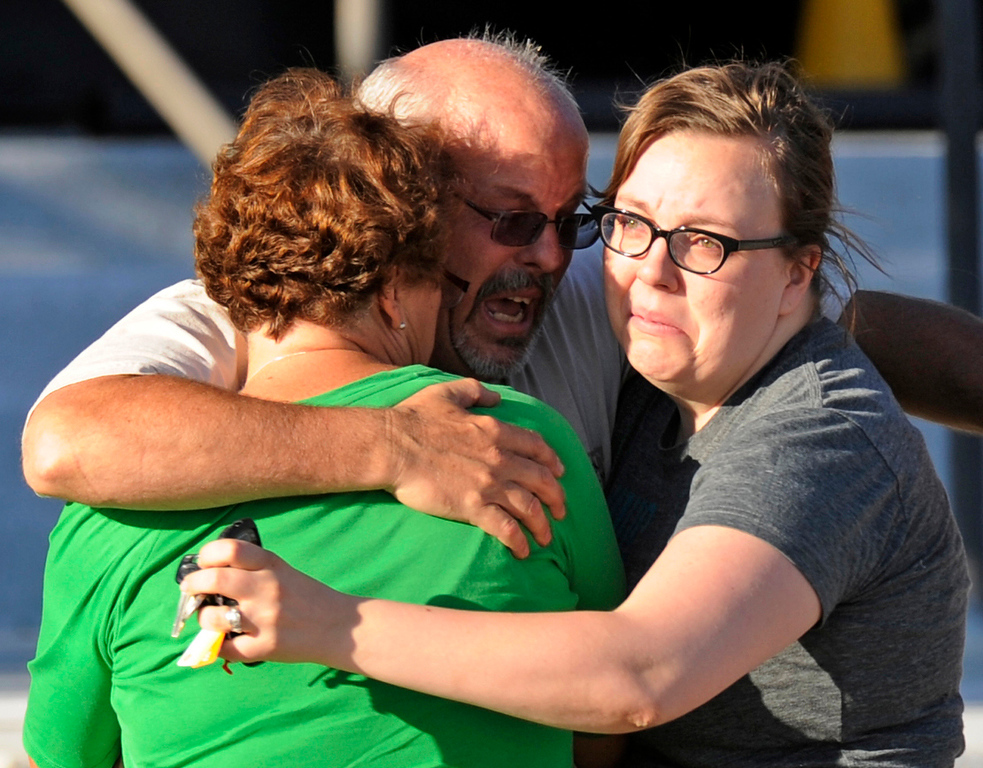 . Tom Sullivan, center, hugs his wife Terry, left, and daughter Megan outside Gateway High School, Friday, July 20, 2012, in Aurora. Sullivan was still missing his son, Alex, after a gunman opened fire at a crowded movie theater. Alex would later be identified as one of twelve people fatally shot in the massacre. RJ Sangosti, The Denver Post