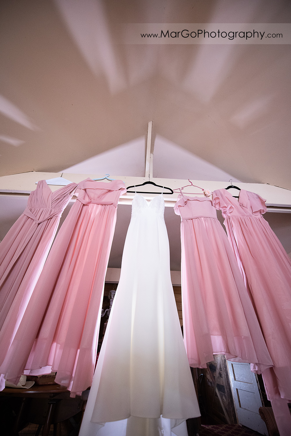 white bridal and pink bridesmaids dresses hanging from the ceiling at Long Branch Saloon & Farms in Half Moon Bay