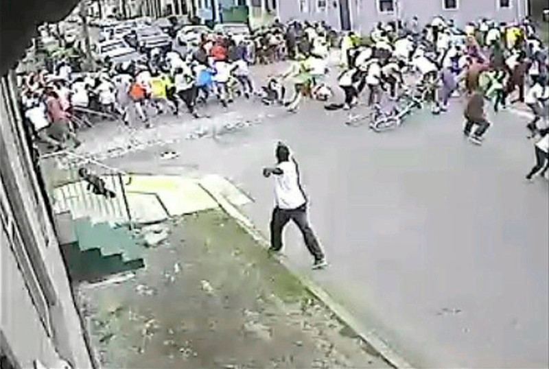 . A still image taken from security camera video released by the New Orleans Police Department (NOPD) shows a gunman shooting into a crowd gathered for a Mother\'s Day second line parade in New Orleans, Louisiana May 12, 2013. Police continued their search on Monday for the gunman, who wounded 19 people, including two children at the parade, a police spokesman said.  REUTERS/NOPD8th/Handout via Reuters