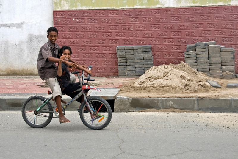 Two kids smiling to the camera while riding a bike in the streets of Dili, East Timor