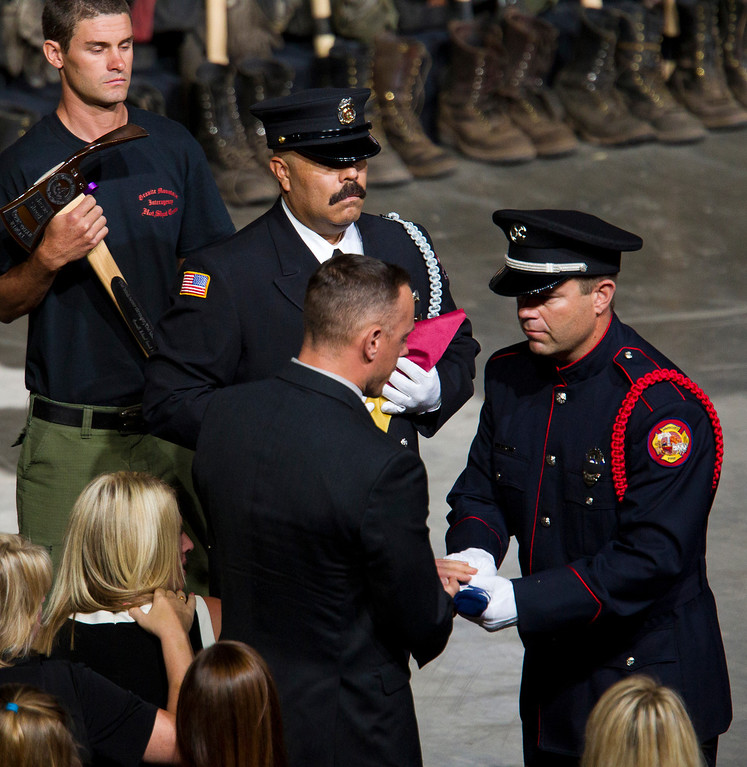 . A flag is presented to the family of fallen firefighter Jesse Steed during a memorial service for the 19 fallen firefighters at Tim\'s Toyota Center in Prescott Valley, Ariz. on Tuesday, July 9, 2013.   (AP Photo/The Arizona Republic, Michael Chow, Pool)