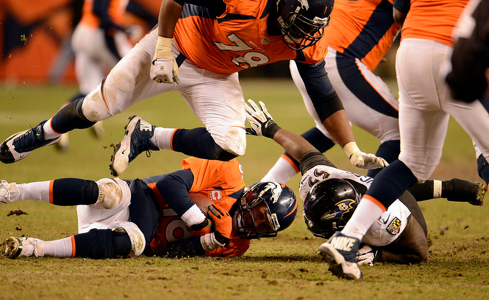 . Denver Broncos quarterback Peyton Manning (18) gets sacked by Baltimore Ravens outside linebacker Terrell Suggs (55) making it fourth down and nine during the second half.  The Denver Broncos vs Baltimore Ravens AFC Divisional playoff game at Sports Authority Field Saturday January 12, 2013. (Photo by John Leyba,/The Denver Post)