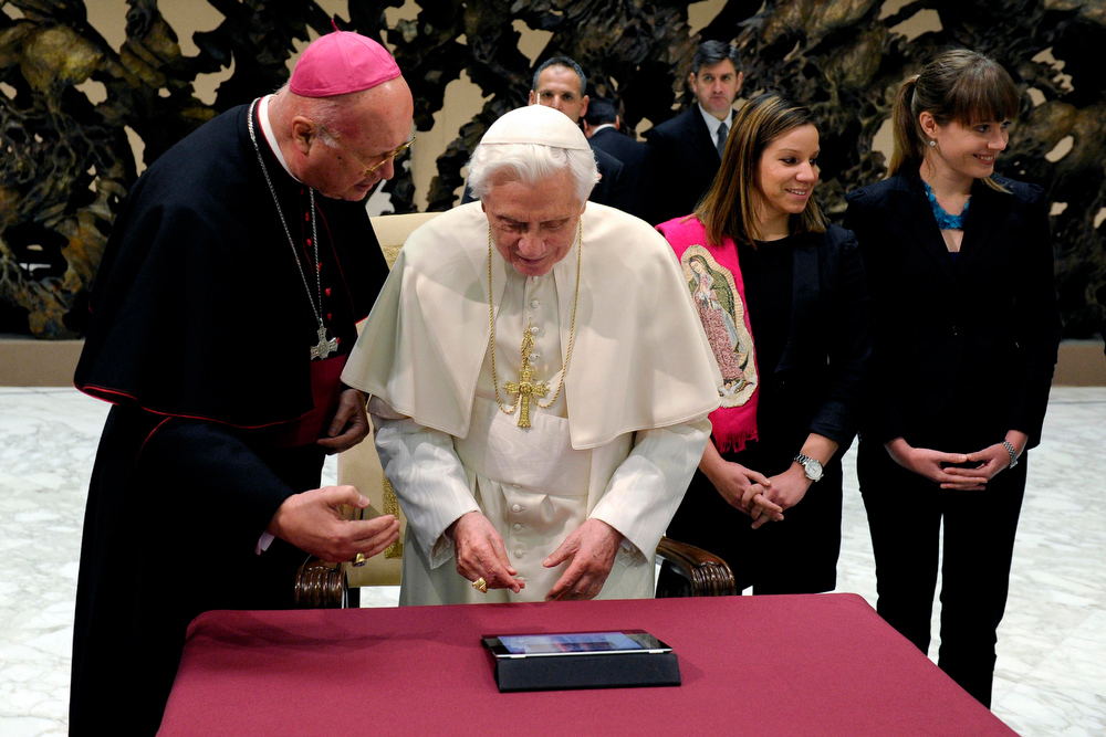 Description of . Pope Benedict XVI (C) posts his first tweet using an iPad tablet after his Wednesday general audience in Paul VI's Hall at the Vatican December 12, 2012. REUTERS/Osservatore Romano