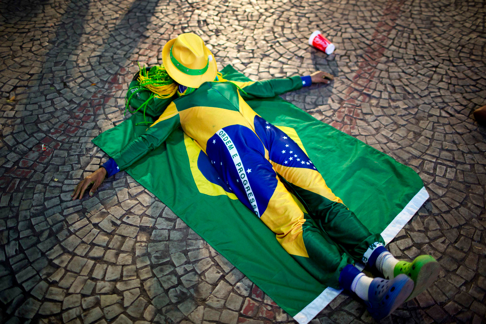 . A Brazil soccer fan rests covered with Brazil\'s national flag after his team won a World Cup round of 16 match against Chile inside the FIFA Fan Fest area in Sao Paulo, Brazil, Saturday, June 28, 2014. (AP Photo/Rodrigo Abd)
