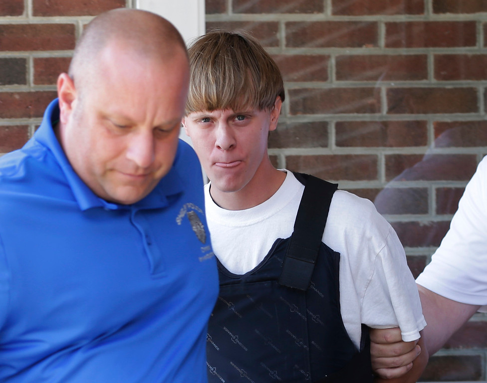 . Charleston, S.C., shooting suspect Dylann Storm Roof, center, is escorted from the Shelby Police Department in Shelby, N.C., Thursday, June 18, 2015. Roof is a suspect in the shooting of several people Wednesday night at the historic The Emanuel African Methodist Episcopal Church in Charleston, S.C. (AP Photo/Chuck Burton)