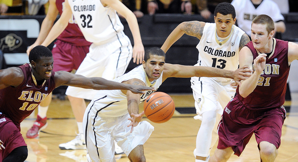 . Xavier Talton of CU runs down the loose ball past Austin Hamilton (10) and Ryley Beaumont of Elon during the second half of the December 13, 2013 game in Boulder. (Cliff Grassmick/Boulder Daily Camera)