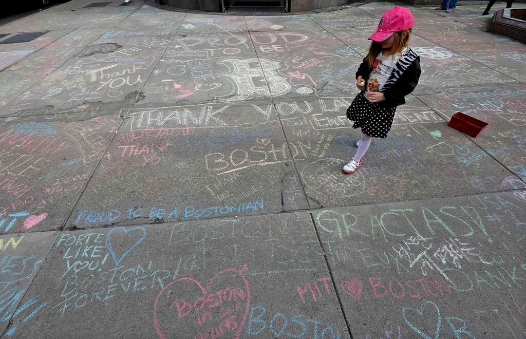 . Jane Cosmas, 4-years-old, of Somerville, Massachusetts, walks amidst hundreds of chalk messages written by passersby about the Boston Marathon bombings on Newbury Street near the scene of the blasts in Boston, Massachusetts, April 20, 2013. REUTERS/Jim Bourg