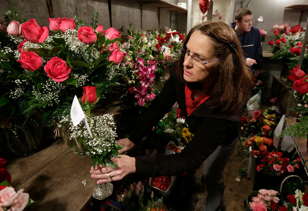 . Patti Miller, of East Lawn Florists gets a flower arrangement from the cooler of  for a Valentines Day delivery in Sacramento, Calif., Friday, Feb. 14, 2014.(AP Photo/Rich Pedroncelli)