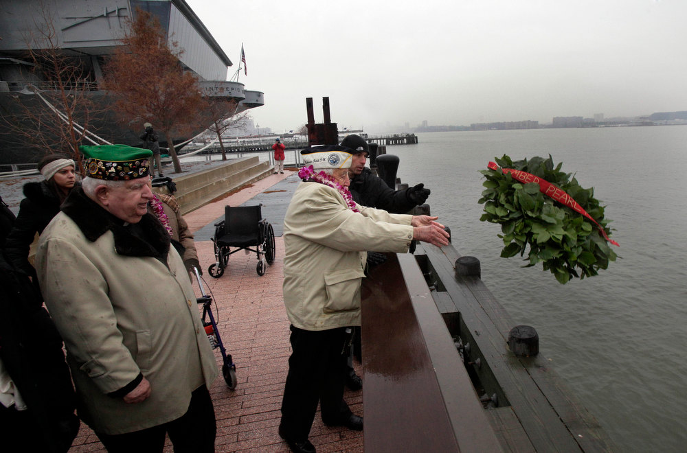 Description of . Pearl Harbor survivor Armando Chick Galella, right, age 91, of Sleepy Hollow, N.Y., tosses a wreath into the Hudson River during ceremonies at the Intrepid Sea, Air and Space Museum. in New York, commemorating the 71st anniversary of the attack at Pearl Harbor, Friday, Dec. 7, 2012. President Barack Obama marked the day on Thursday by issuing a presidential proclamation, calling for flags to fly at half-staff on Friday and asking all Americans to observe the day of remembrance and honor military service members and veterans. (AP Photo/Richard Drew)