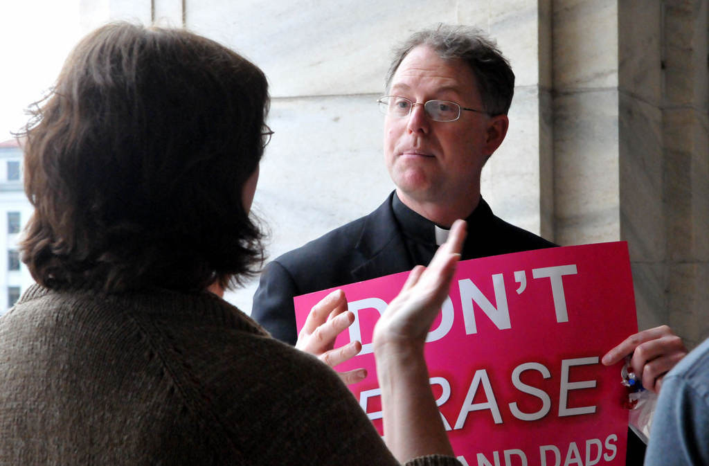 . Roman Catholic priest the Rev. Thomas McCabe, who opposes gay marriage, speaks with a gay-marriage supporter at the state Capitol in St. Paul on Thursday, May 9, 2013, before the House floor vote. McCabe is the pastor at Immaculate Conception Church in Lonsdale, Minn. (Pioneer Press: John Doman)