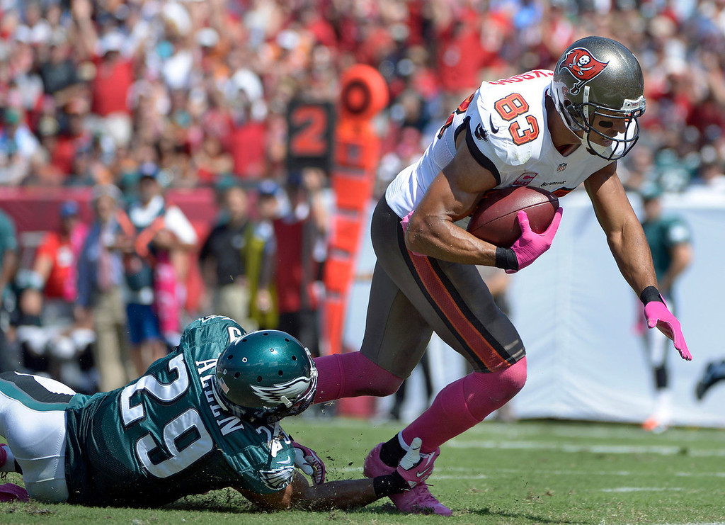 . Tampa Bay Buccaneers wide receiver Vincent Jackson (83) is tripped up by Philadelphia Eagles strong safety Nate Allen (29) but scores on a 24-yard touchdown reception during the second quarter of an NFL football game Sunday, Oct. 13, 2013, in Tampa, Fla. (AP Photo/Phelan M. Ebenhack)