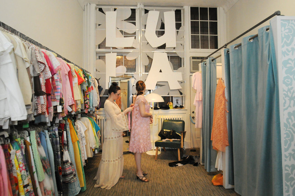 . Melissa Heen, left, a soon-to-be bride fastens the back of her bridesmaid, Cassandra Monson\'s, dress at Lula\'s as they shopped on April 27, 2013 for dresses for Heen\'s upcoming wedding. (Pioneer Press: Ginger Pinson)   (Pioneer Press: Ginger Pinson)