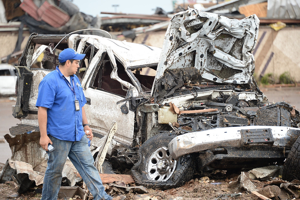 . A man observes a destroyed car at the Moore hospital parking lot. 