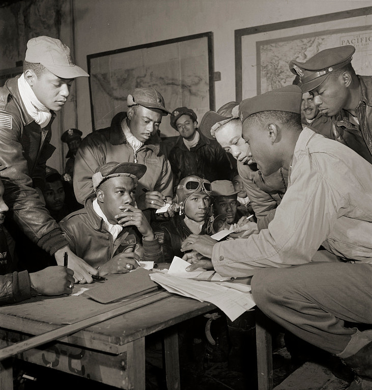 ". The Tuskegee Airmen were the first African-American military aviators in the United States armed forces. Several Tuskegee airmen at Ramitelli, Italy, March, 1945. Front row, left to right: unidentified airman; Jimmie D. Wheeler (with goggles); Emile G. Clifton (cloth cap) San Francisco, CA, Class 44-B. Standing left to right: Ronald W. Reeves (cloth cap) Washington, DC, Class 44-G; Hiram Mann (leather cap); Joseph L. ""Joe\"" Chineworth (wheel cap) Memphis, TN, Class 44-E; Elwood T. Driver? Los Angeles, CA, Class 44-A; Edward \""Ed\"" Thomas (partial view); Woodrow W. Crockett (wheel cap); at Ramitelli, Italy, March 1945. (Source: Tuskegee Airmen 332nd Fighter Group pilots.) Toni Frissell, photographer. Library of Congress"