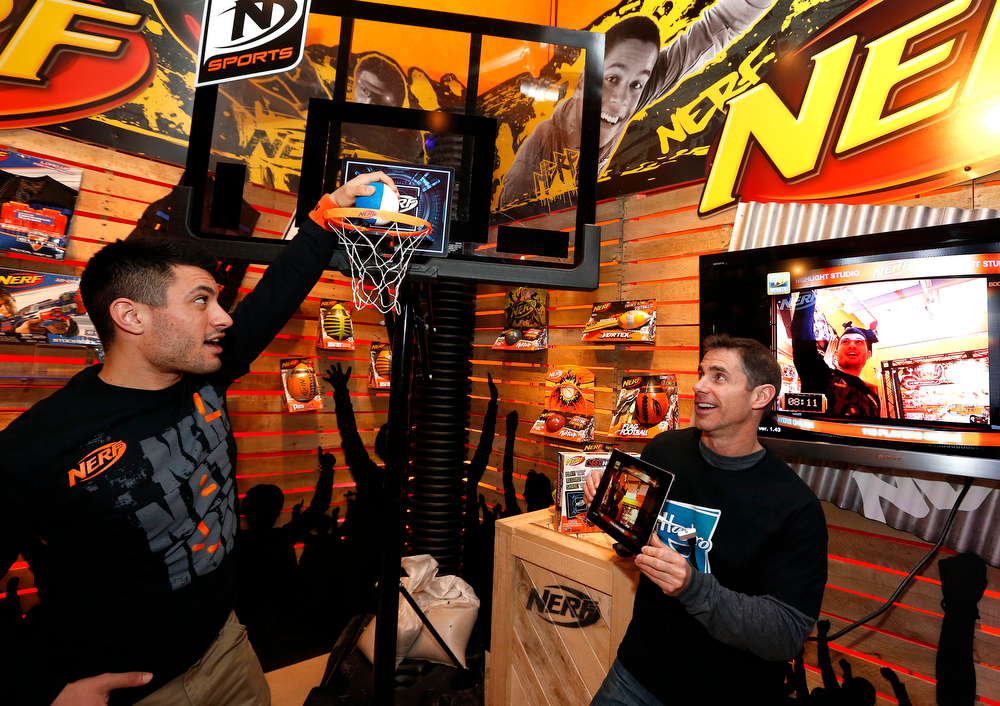 Description of . Demonstrators L.J. Regine, left, and Brian McMullan records their shots while playing with the NERF N-SPORTS CYBERHOOP set in Hasbroís showroom at the American International Toy Fair, Saturday, Feb. 9, 2013, in New York.  The CYBERHOOP set works with a free app to track game stats, capture games on video, and provide commentary. The CYBERHOOP app also allows players to play virtually and share highlights with friends online. (Photo by Jason DeCrow/Invision for Hasbro/AP Images)
