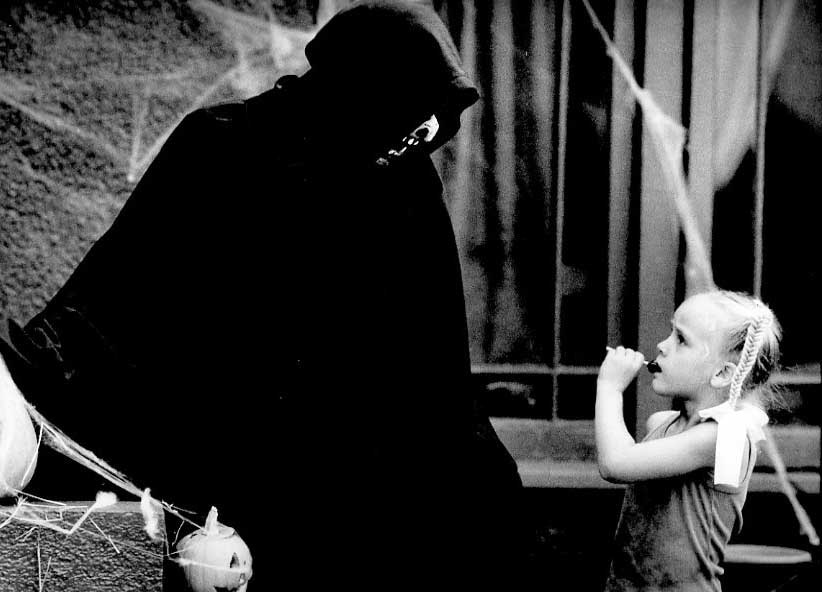 . 1987: Jennifer Asher, 7, accepts candy from ghoul Richard Geary, San Jose. (Len Lahman, Mercury News)