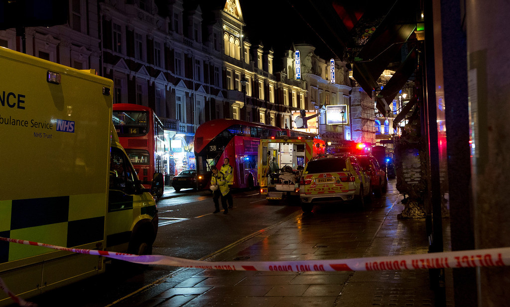 . Emergency service vehicles gathered among London buses  following an incident  during a performance at the Apollo Theatre, far right, in London\'s Shaftesbury Avenue, Thursday evening, Dec. 19, 2013. (AP Photo by Joel Ryan, Invision)