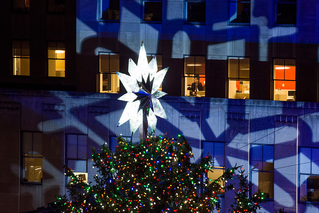 . A man looks at the Rockefeller Center Christmas tree that stands lit at Rockefeller Center during the 85th annual Rockefeller Center Christmas tree lighting ceremony, Wednesday, Nov. 29, 2017, in New York. (AP Photo/Andres Kudacki)