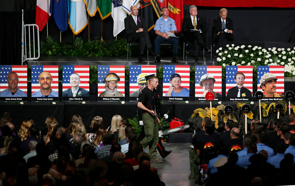 . Surviving Hotshot crew member Brendan McDonough walks back to his seat at a memorial service after presenting the U.S. flag to families of the fallen members of the Granite Mountain Hotshots, in Prescott Valley, Arizona July 9, 2013.REUTERS/Lucy Nicholson