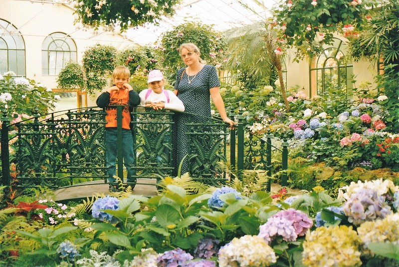 boomer woman with two kids exploring a botanical garden