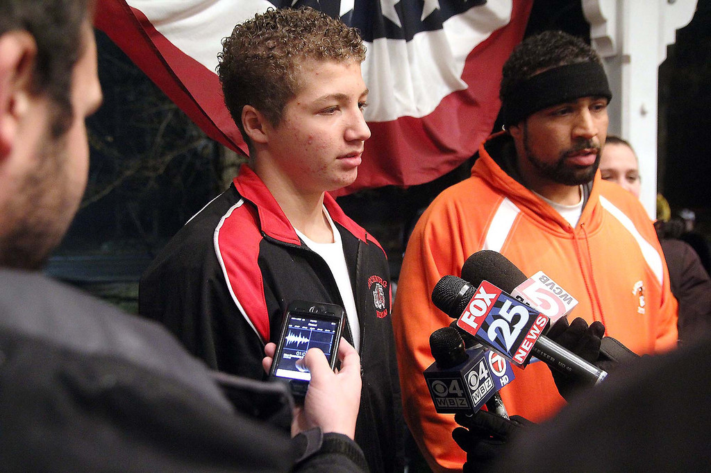 . Lunenburg eighth graders Isaac Phillips talks to the press at the Lunenburg gazebo during a ceremony to support him on Sunday night. Next to him is his father Anthony Phillips. SENTINEL & ENTERPRISE/ JOHN LOVE