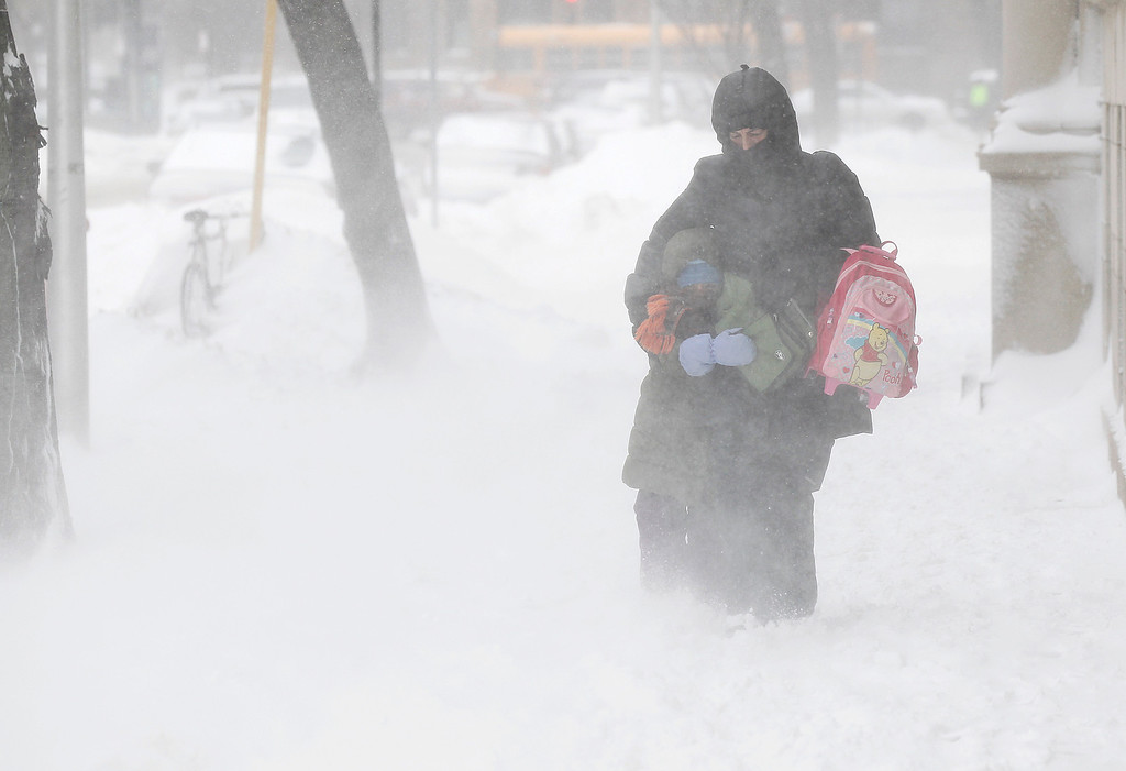 . Commuters bundle up together as they walk against blowing snow Wednesday, Feb. 5, 2014, in Chicago. Heavy, blowing snow is moving across much of Illinois as the state gets pelted by the latest round of winter weather. (AP Photo/Kiichiro Sato)