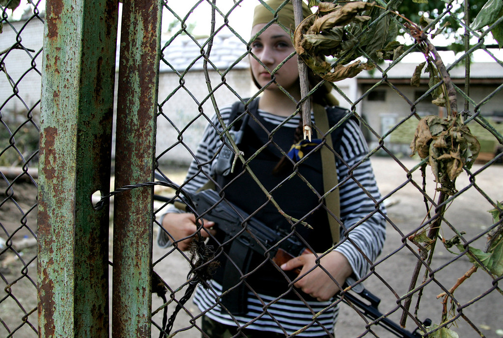 . Alina, no second name available, a volunteer of the Ukrainian national guard, stands behind a fence at a base in Starobelsk, Luhansk region, eastern Ukraine, Sunday, May 25, 2014. Ukraine\'s critical presidential election went underway Sunday under the wary scrutiny of a world eager for stability in the country. An exit poll showed that billionaire candy-maker Petro Poroshenko won election in the first round. (AP Photo/Alexander Ermochenko)