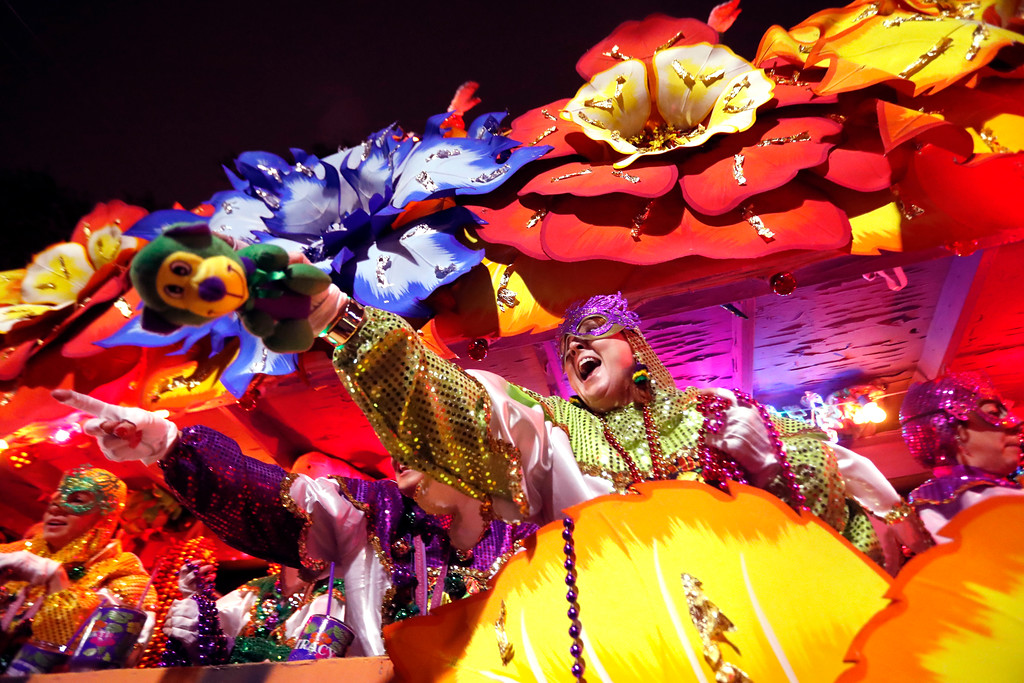 . Float riders toss trinkets as the Krewe of Orpheus rolls in New Orleans, Monday, Feb. 12, 2018. (AP Photo/Gerald Herbert)