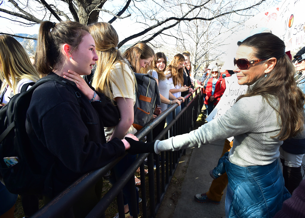. Lyra Mayfield reaches out to hold Lily Chavkin\'s hand as the Boulder High student becomes emotional talking to the crowd across the fence to the school property during a walkout to protest gun violence at Boulder High School on Wednesday morning.  For more photos go to dailycamera.com Paul Aiken Staff Photographer March 14, 2018.
