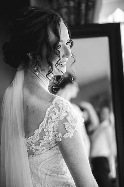 The bride smiling, looking over her shoulder.