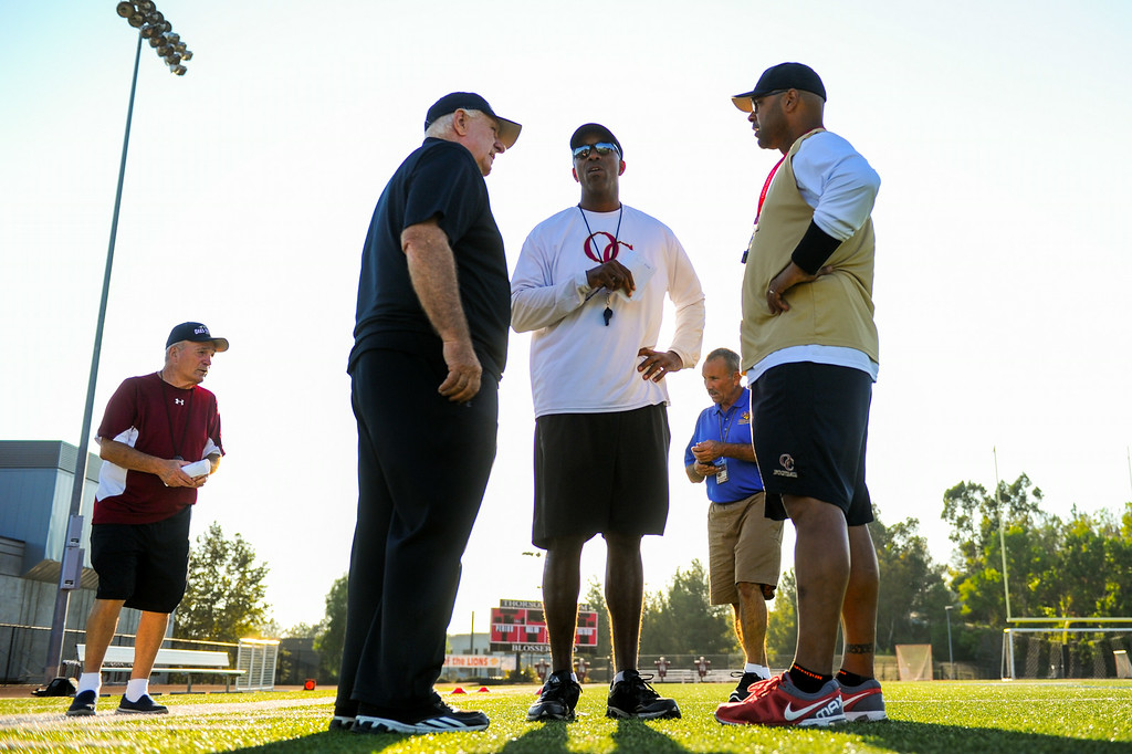 . Oaks Christian High School football head coach Bill Redell, second from left, talks with his staff before practice, Wednesday, August 20, 2014. (Photo by Michael Owen Baker/Los Angeles Daily News)