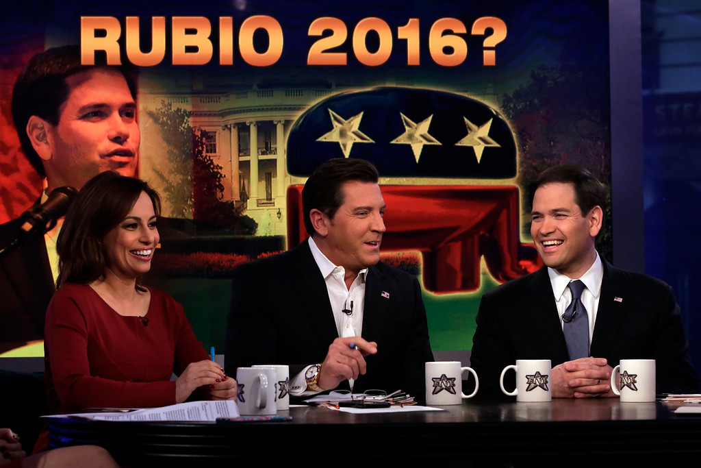 ". Co-hosts Julie Roginsky, and Eric Bolling, center, interview U.S. Sen. Marco Rubio, R-Fla., on ""The Five\"" television program, on the Fox News Channel, in New York, Monday, March 30, 2015. Closing in on an expected announcement that he will run for president, Sen. Marco Rubio said Monday that he is planning a political event in two weeks in Miami to announce his 2016 plans. The first-term Republican from Florida, appearing on Fox News, did not explicitly say he is running for the White House, instead telling would-be supporters to go to his website and reserve tickets for the rally. (AP Photo/Richard Drew)"