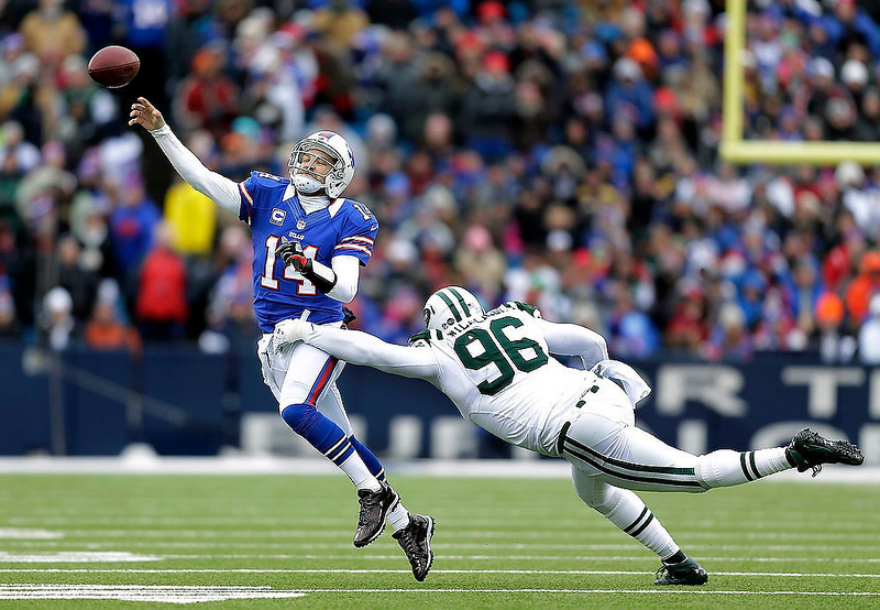 . Buffalo Bills quarterback Ryan Fitzpatrick (14) throws a pass under as New York Jets defensive end Muhammad Wilkerson (96) tries to make a tackle during the second half of an NFL football game on Sunday, Dec. 30, 2012, in Orchard Park, N.Y. (AP Photo/Gary Wiepert)