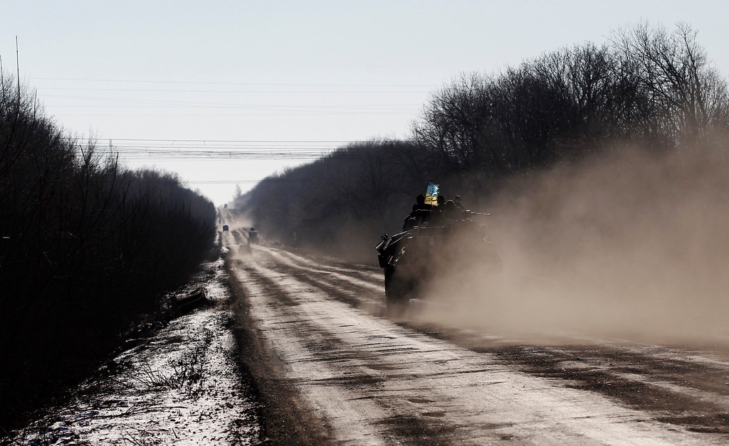 . A Ukrainian armored vehicle passes on a road stretching away from the town of Artemivsk, Ukraine, towards Debaltseve, Tuesday, Feb. 17, 2015. Ukrainian government troops and Russia-backed rebels failed Tuesday to start pulling back heavy weaponry from the front line in eastern Ukraine as a deadline passed to do so. Under a cease-fire agreement negotiated by the leaders of Ukraine, Russia, Germany and France last week, the warring sides were to begin withdrawing heavy weapons from the front line on Tuesday. (AP Photo/Petr David Josek)